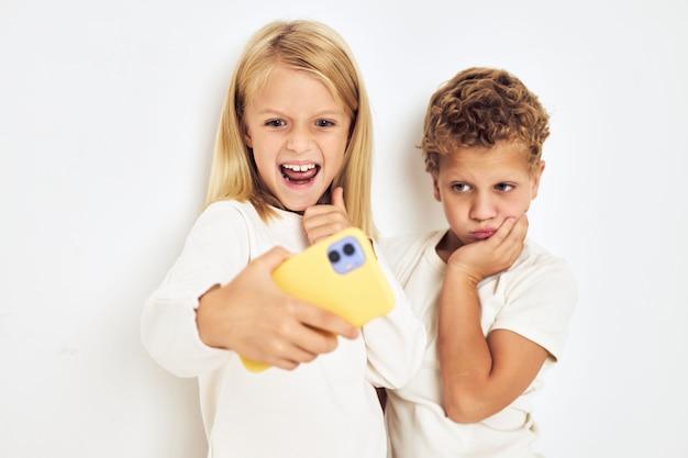 Twee kleuters jongen en meisje met gele telefoon entertainment levensstijl jeugd