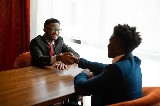 Twee knappe afrikaanse mannen in pakken binnenshuis handen schudden
