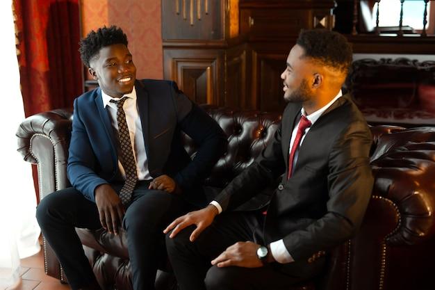 Twee knappe afrikaanse mannen in pakken binnenshuis