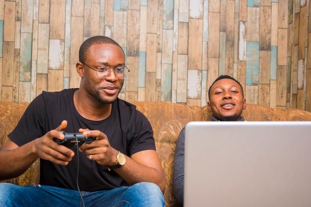 Twee knappe afrikanen die op de bank zitten en videogames spelen met joystick, gamepad, pad