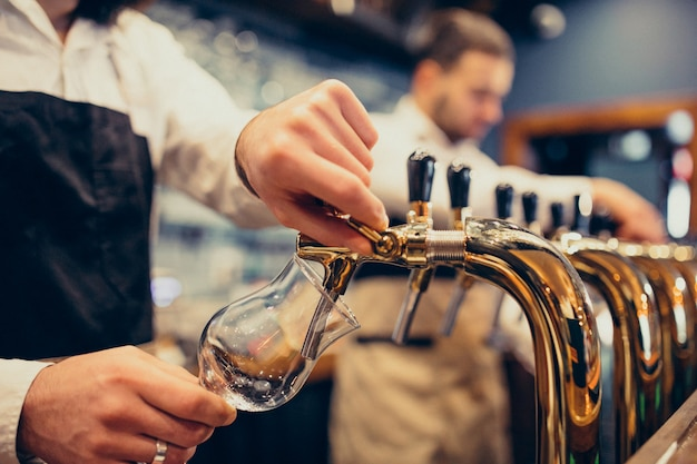 Twee knappe barmannen die bier porren bij bar