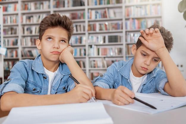 Twee knappe jonge tweelingjongens zien er moe en verveeld uit en maken samen huiswerk in de bibliotheek