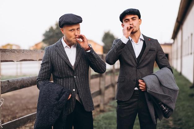 Twee knappe mannen in pak roken op de boerderij