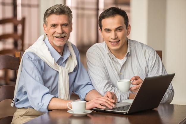 Twee knappe zakenlieden gebruiken laptop.