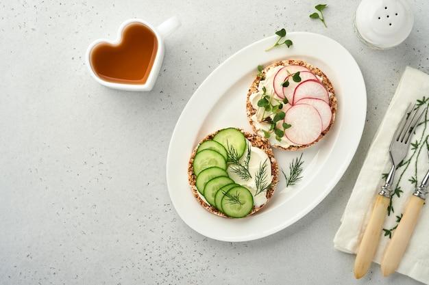 Twee knapperige boekweitbroodcake glutenvrij met roomkaas, rode radijs, komkommer en microgroen voor een gezond ontbijt op grijze stenen achtergrond. uitzicht van boven. concept veganistisch en gezond eten.