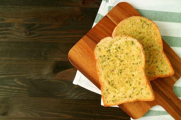 Twee knoflook boter toasts op houten plaat geserveerd op donkere bruine tafel met servet