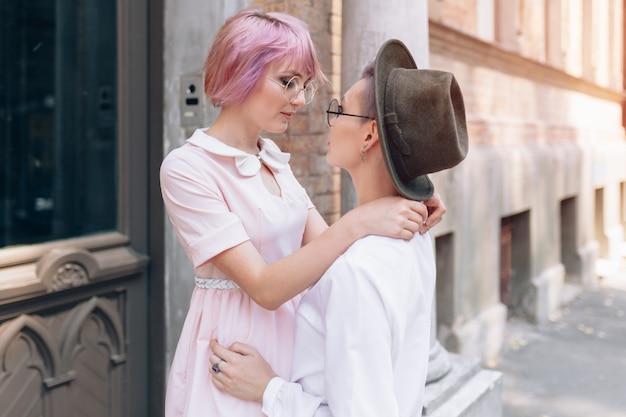 Twee knuffelen meisjes in de buurt van het gebouw in de stad