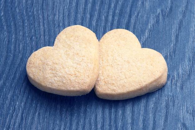 Twee koekjes in de vorm van een hart op een donkere houten plank. dessert eten