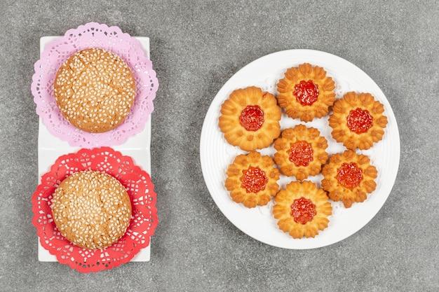 Twee koekjes met sesamzaadjes en gelei koekjes in marmeren oppervlak