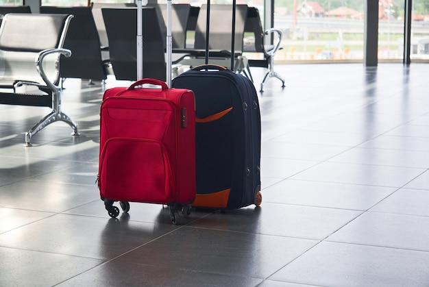Twee koffers liggen op de grond in de wachtkamer van de luchthaven