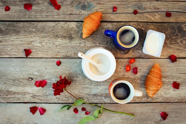 Twee koffie, croissants, suiker, snoep, yoghurt, roos en bloemblaadjes op oud hout