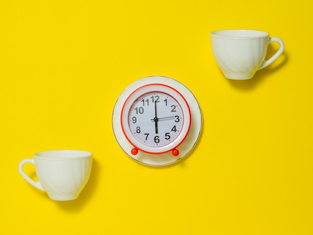Twee koffiekopjes en een rode wekker op een witte schotel op een gele achtergrond. het concept van het opheffen van de toon in de ochtend. plat leggen.