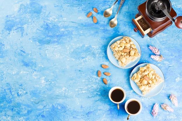 Twee koffiekoppen, koffiemolen en appeltaart op artistiek blauw. bovenaanzicht