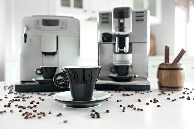 Twee koffiemachines in de huiskeuken met een houten container met koffiebonen.