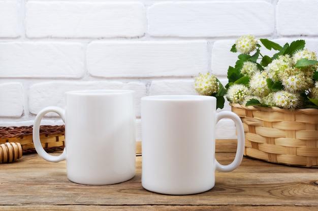 Twee koffiemok mockup met mand met bloemen