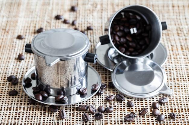 Twee koffiezetapparaten met verspreide gehele koffiebonen op placemat.