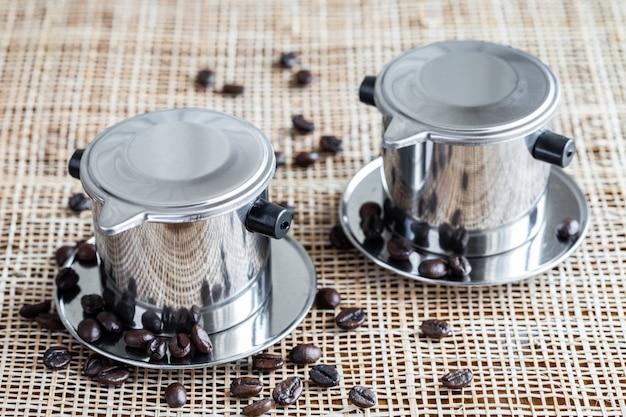Twee koffiezetapparaten met verspreide hele koffiebonen op placemat.