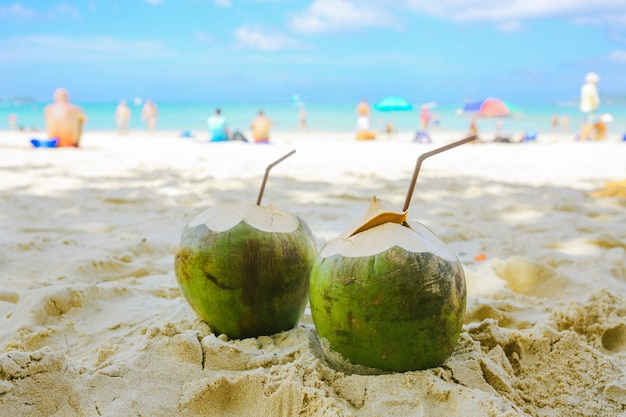 Twee kokosnoten met rietjes liggen op het strand op de achtergrond van het strand met mensen. vooraanzicht