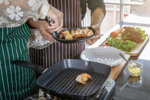 Twee koks helpen garnalen bakken in de keuken.