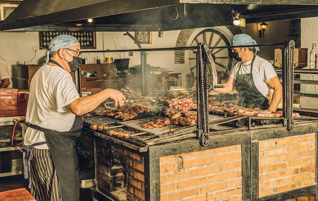 Twee koks met gezichtsmaskers en haarnetjes koken vlees in de grill en gebruiken vleestangen.