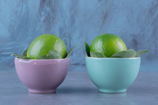 Twee kommen citroenen op marmeren tafel.