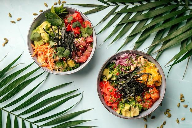 Twee kommen hawaiiaanse gezonde poke-mixen met tonijn en zalm