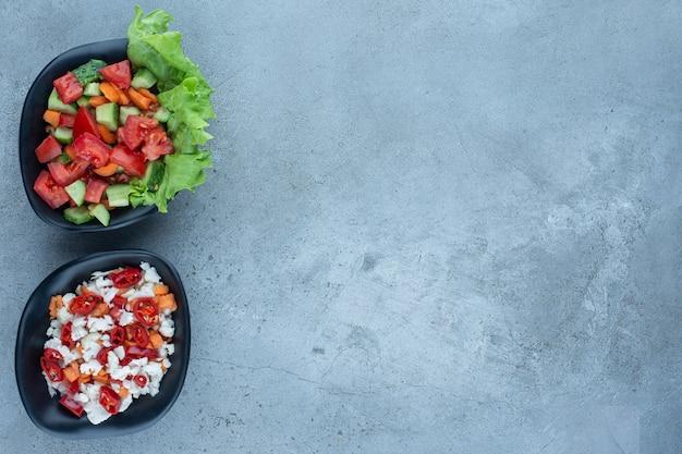 Twee kommen herderssalade naast een kom peper- en bloemkoolsalade op marmer.