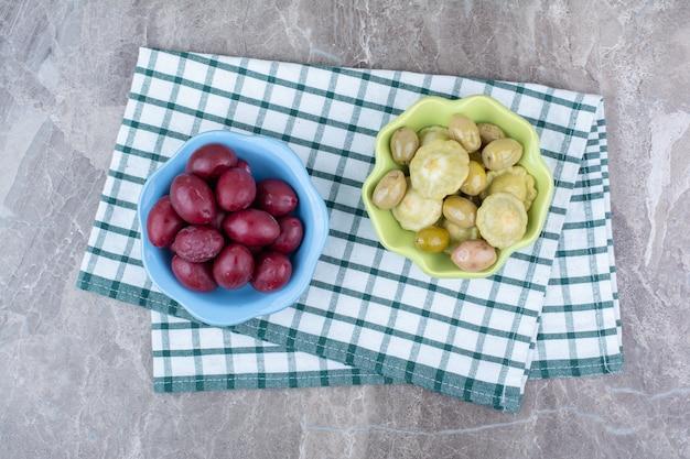 Twee kommen ingelegde groenten en pruimen met tafelkleden.