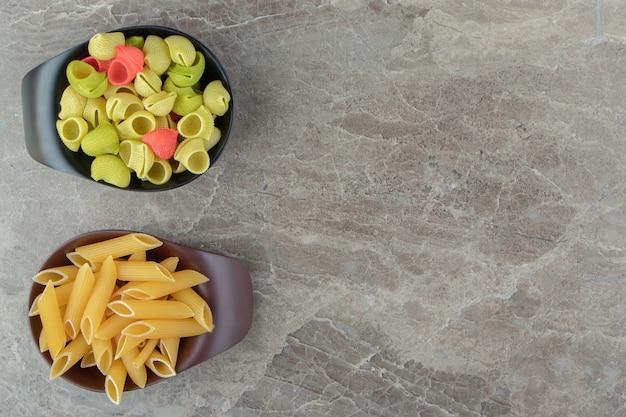 Twee kommen kleurrijke zeeschelp en penne pasta op marmeren oppervlak