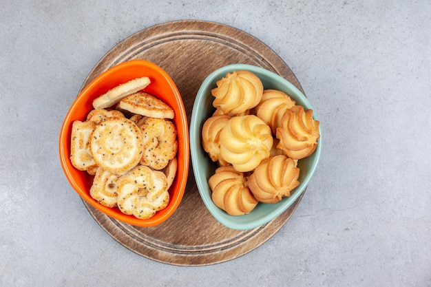Twee kommen koekje en koekjeschips op houten bord op marmeren achtergrond. hoge kwaliteit foto
