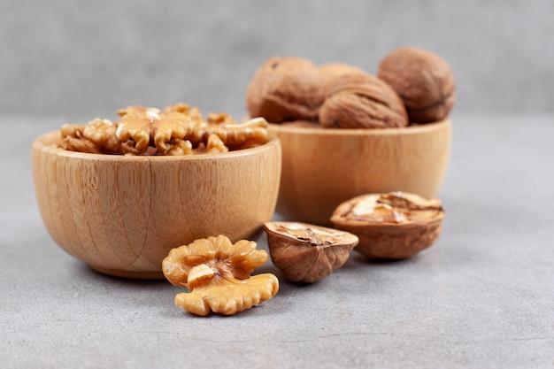 Twee kommen met hele en gebarsten walnoten op marmeren achtergrond. hoge kwaliteit foto