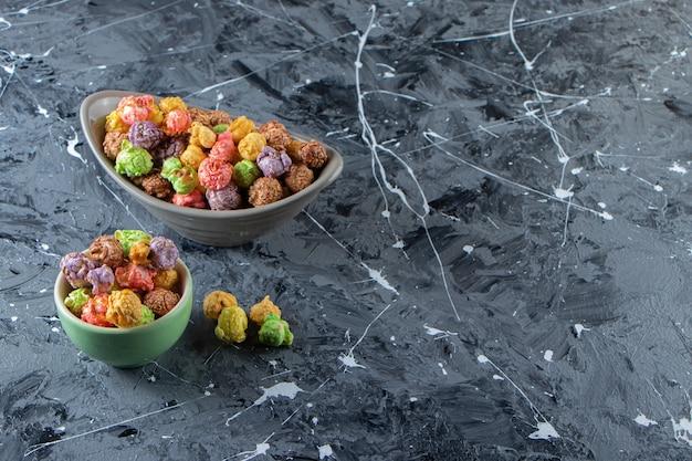 Twee kommen met kleurrijke smakelijke popcorns op marmeren oppervlak.