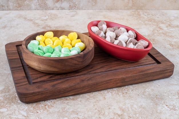Twee kommen met kleurrijke snoepjes op een houten bord