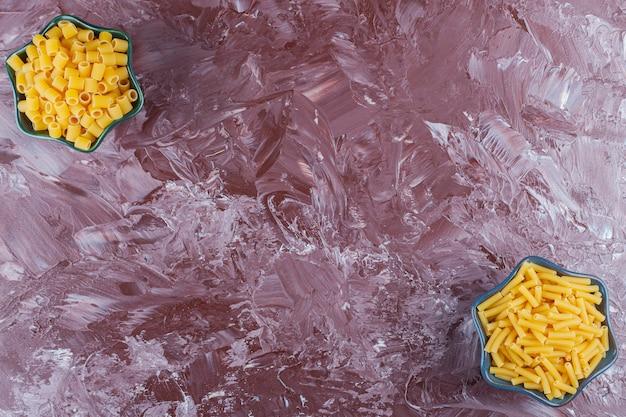 Twee kommen met verschillende soorten rauwe droge pasta op een lichte tafel.