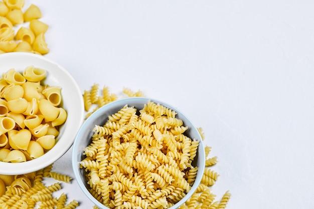 Twee kommen ongekookte pasta's op witte achtergrond