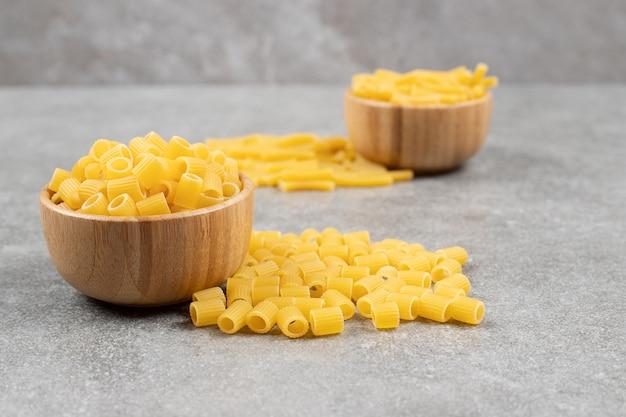 Twee kommen rauwe macaroni op marmeren oppervlak