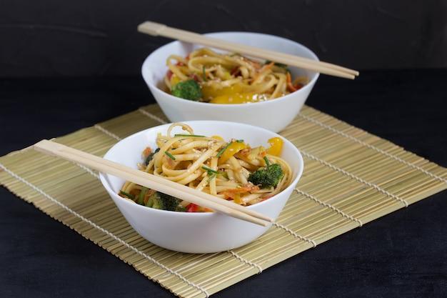 Twee kommen roerbak udonnoedels met groenten en sojasaus op een bamboemat
