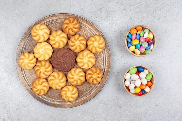 Twee kommen snoep naast een decoratief arrangement van koekjes op een houten bord op een marmeren oppervlak.