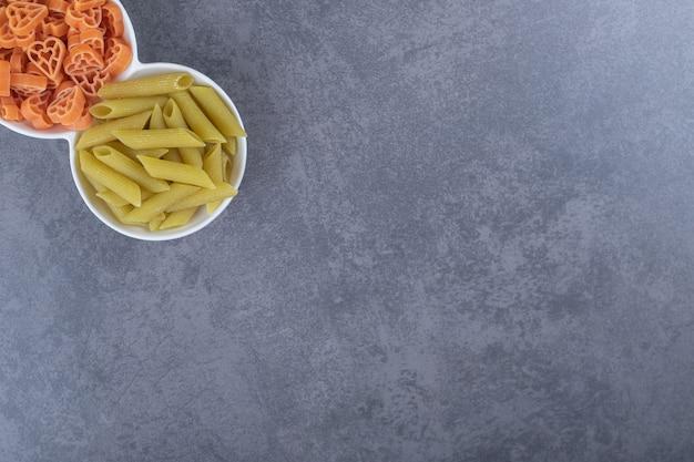 Twee kommen van verschillende pasta op stenen achtergrond.