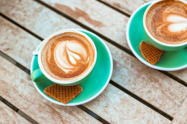 Twee kop koffie met hartvorm latte kunst en wafel