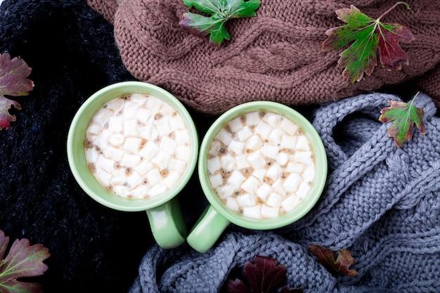 Twee kop koffie of warme chocolademelk met marshmallow in de buurt van gebreid.