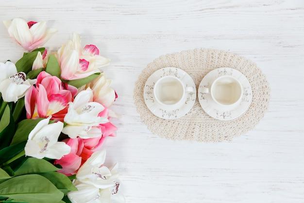 Twee kopje en verse tulpen op houten tafel, bovenaanzicht.