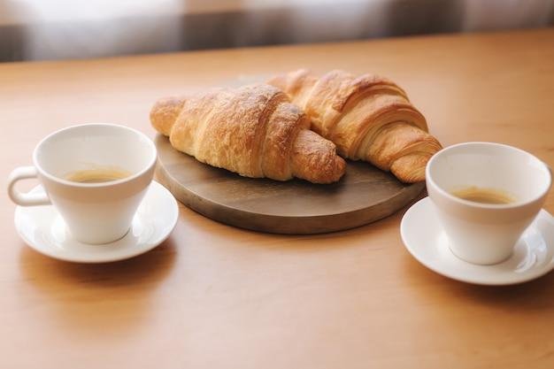 Twee kopje koffie op houten tafel en twee verse croissants. ontbijt thuis.