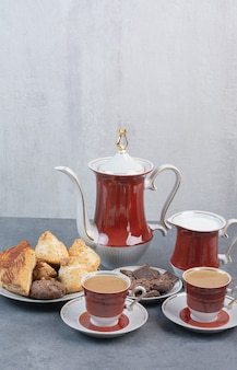 Twee kopjes aromakoffie met gebak op grijze tafel.