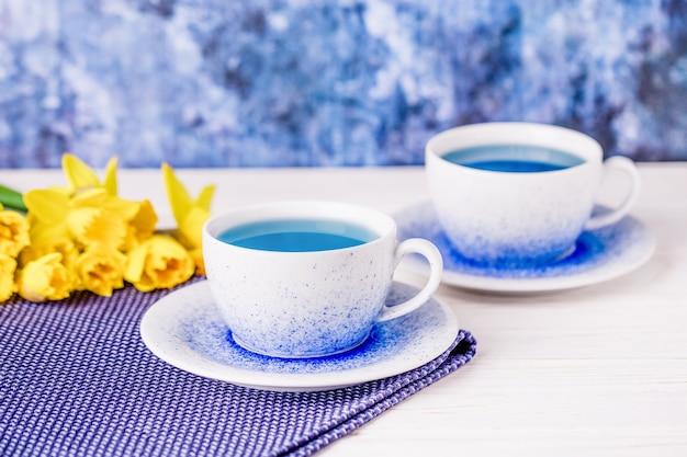 Twee kopjes blauwe thee en een boeket narcissen