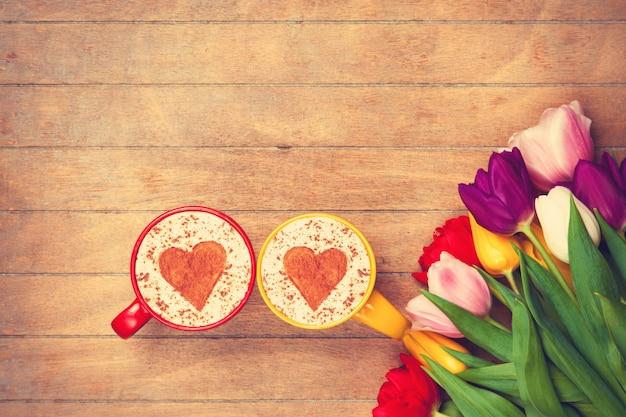 Twee kopjes cappuccino en tulpen