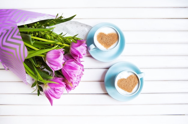 Twee kopjes cappuccino met een hartvormig symbool en paarse tulpen op een houten ondergrond