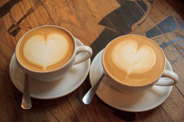 Twee kopjes cappuccino met latte art op houten tafel.