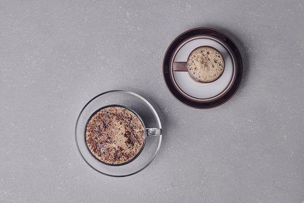 Twee kopjes cappuccino op een grijze achtergrond.