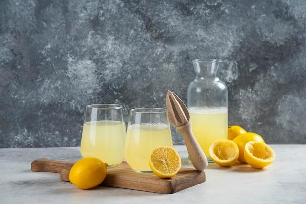 Twee kopjes citroensap op een houten bord.
